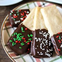 plate of chocolate dipped shortbread cookies with christmas sprinkles