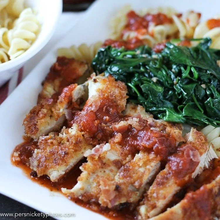 breaded chicken on white plate with marinara and spinach