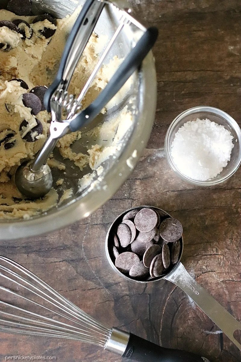 mixing bowl of Salted Chocolate Chip cookie dough, a whisk, and chocolate feves
