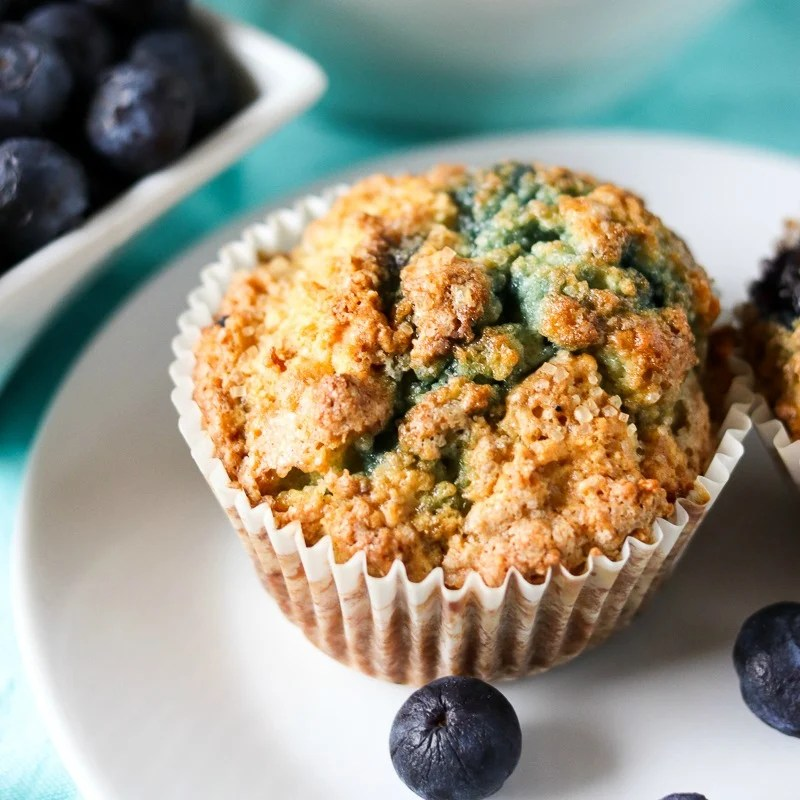These Blueberry Muffins have a tender, buttermilk crumb, are full of blueberry flavor, and are topped with a crunchy sugary topping. Start your day off right with a batch of the best blueberry muffins! | www.persnicketyplates.com