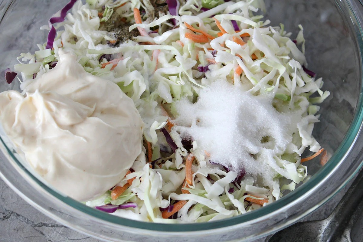 mixing bowl with shredded cabbage, sugar, and miracle whip