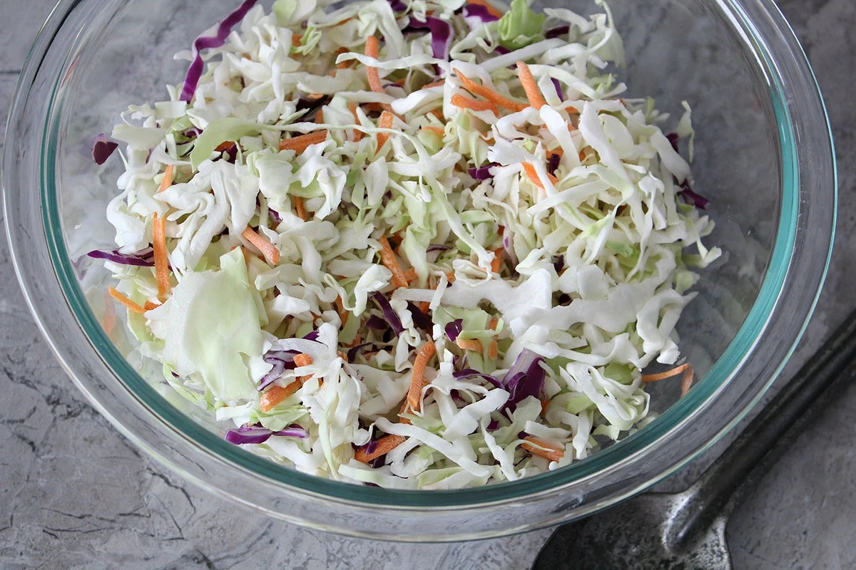 shredded cabbage, carrots, and red cabbage in glass bowl