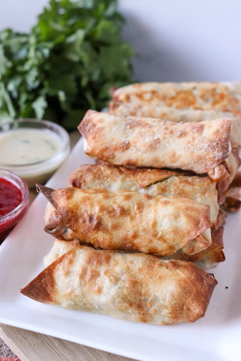 stack of air fryer egg rolls with dipping sauces