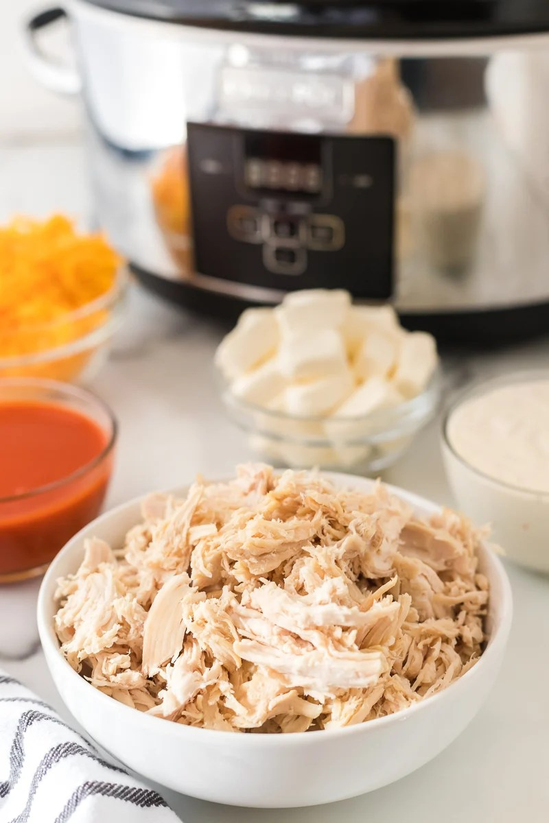 bowl of shredded chicken with slow cooker in background