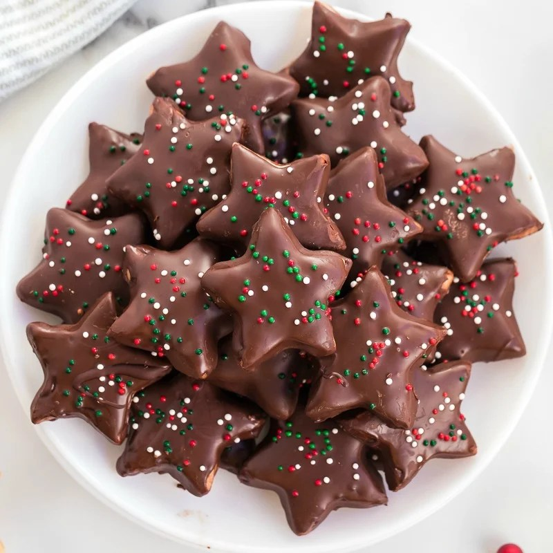 platter of shortbread cookies coated in chocolate with christmas sprinkles
