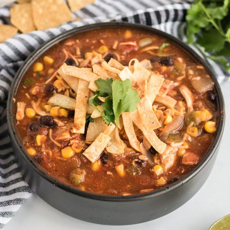 black bowl full of chicken tortilla soup