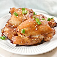 air fried sticky chicken thighs on a white plate with green onion & sesame seed garnish