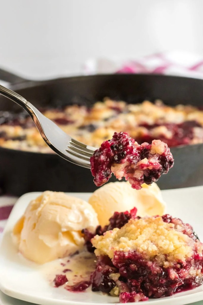 forkful of blackberry crumble served with vanilla ice cream
