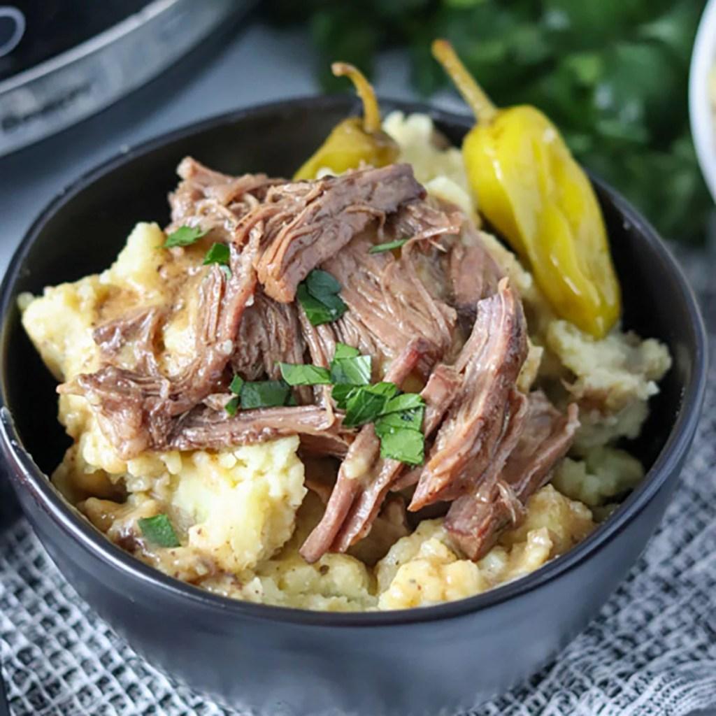 close up on bowl of mississippi pot roast over mashed potatoes