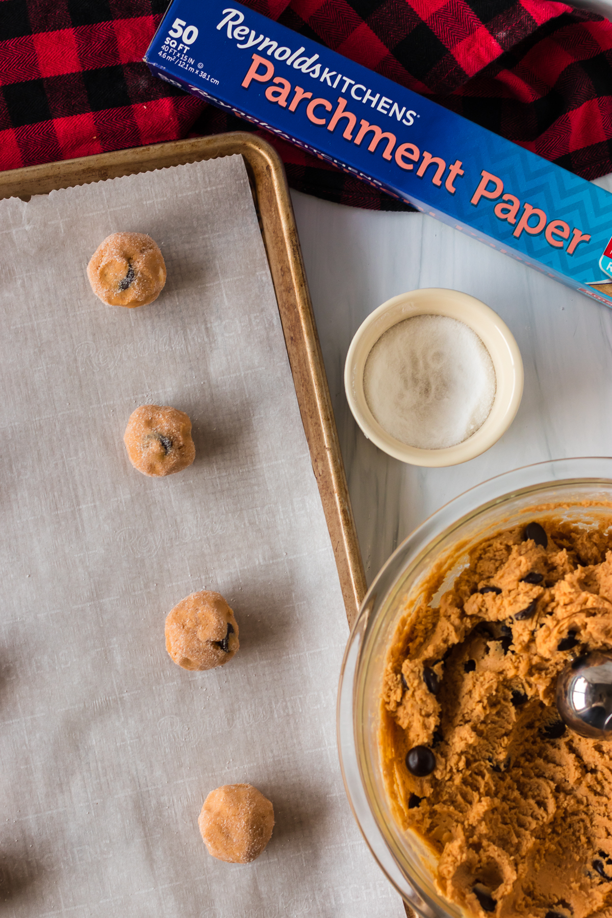overhead shot of cookie dough balls on a baking sheet with reynolds parchment paper