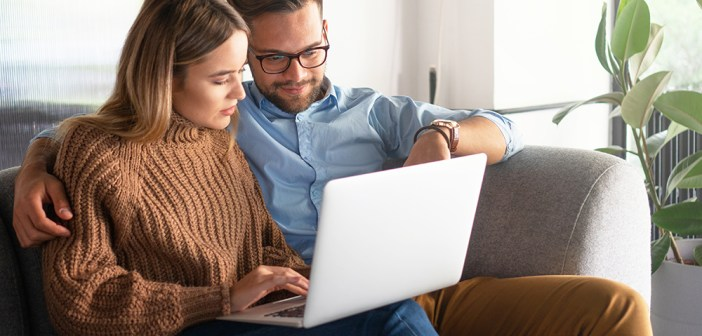 Young couple looking in laptop