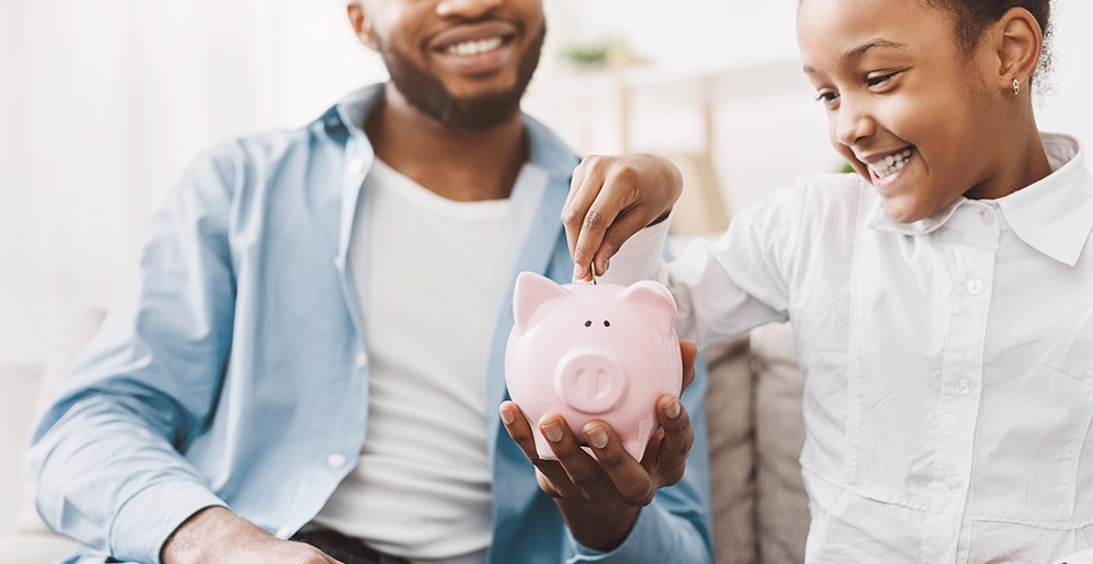Dad and son placing money in pink piggy bank