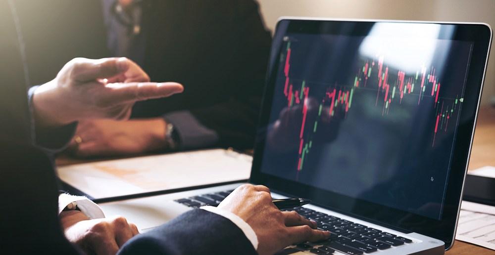 Man in suit using laptop to trade stock