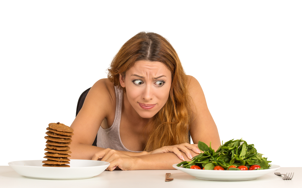 A woman trying to decide if the salad or the cookie diet is right for her.