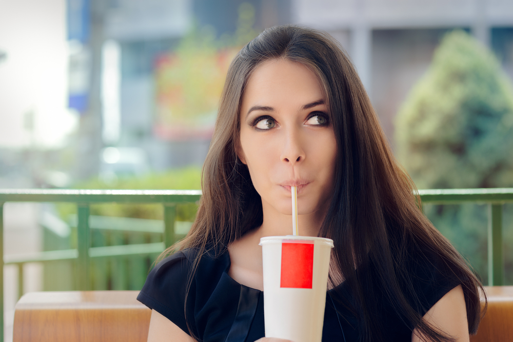 A girl, drinking her large soda while she still can!