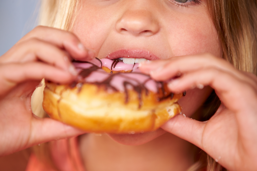 A little girl eating a doughnut as our country suffers from an epidemic of obesity.