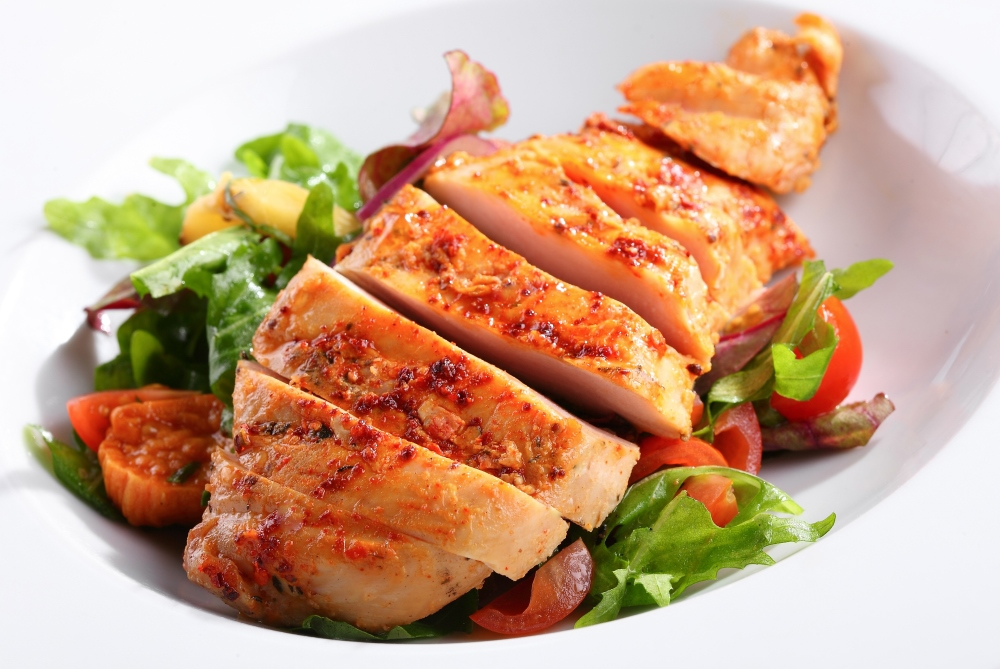 A mouth-watering example of our real marinara chicken breast on a bed of greens with tomatoes.
