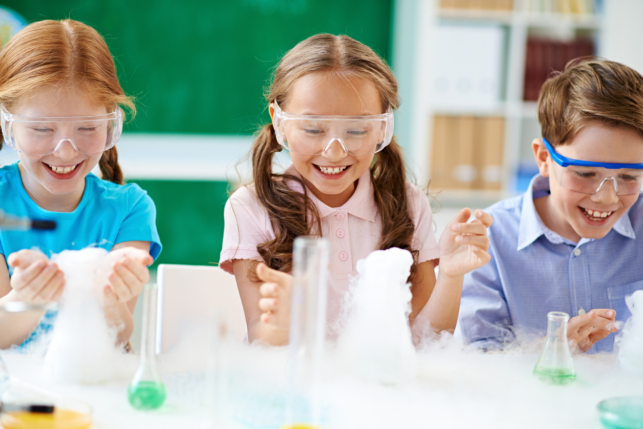 Cheerful elementary students observing chemical reaction with smoke.