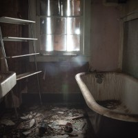 Seeing Between the Cracks - A decaying bathroom in a ghost town house.