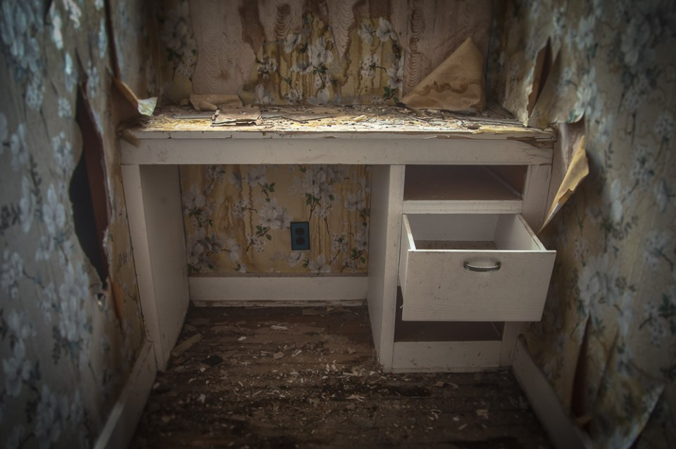The Last Draw - A writing desk sits abandoned in the house of a former mine worker surrounded by peeling wallpaper.