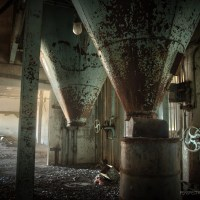 Opening the Flood Gates - Grain funnels rusted and peeling inside an abandoned feedlot.