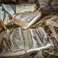 Story Time - Children's book lie crumbling in the dirt at an abandoned orphanage.