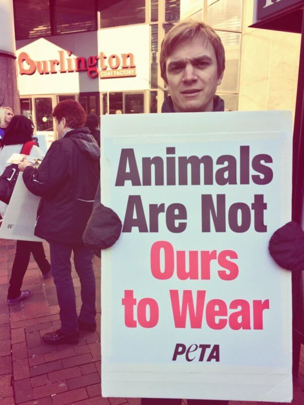 "A PETA staffer holds a sign reading ""Animals Are Not Ours to Wear"" outside Burlington Coat Factory"