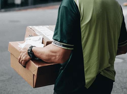 宅配の荷物を抱える人物