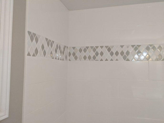 Accent strip and tiles installed in a bathroom