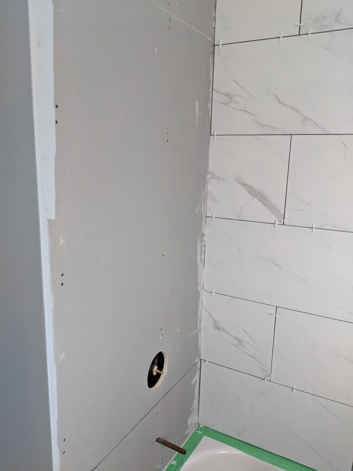 New tiles being installed on to new DenseShield over tub