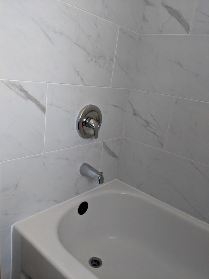 New tub, tiles, shower valve, down spout installed