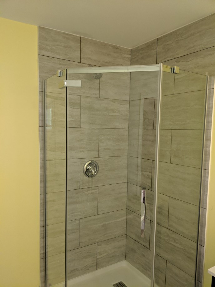 New shower including tiled walls and a glass door
