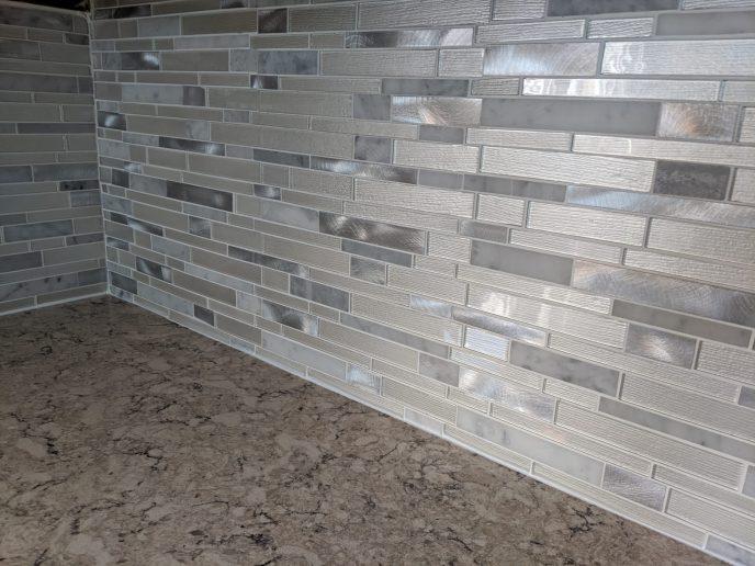 Glass and metal tiles installed for kitchen back splash