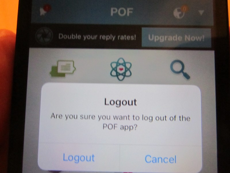Close up of mobile phone with the POF online dating application asking if the user would like to log out of the profile