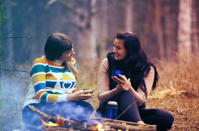 Two people outdoors chatting by a camp fire