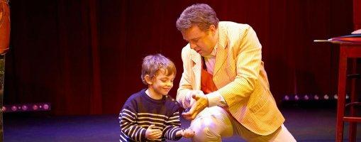 Peter Din et un jeune spectateur côte à côte, accroupi sur scène pendant le spectacle Le Magicien Voyageur. Une photo pleine de tendresse prise au Zèbre de Belleville.