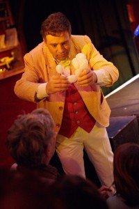 Peter Din lors d'un spectacle magique au Zèbre de Belleville propose un caniche en ballon à un jeune spectateur.