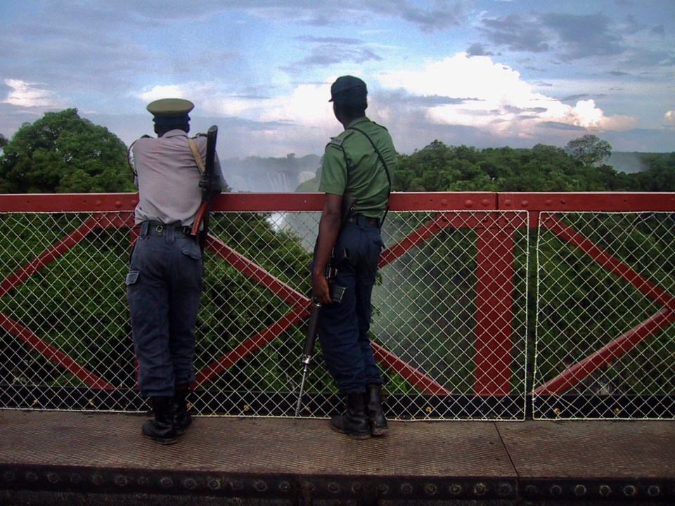 Guards watching Victoria Falls from border bridge