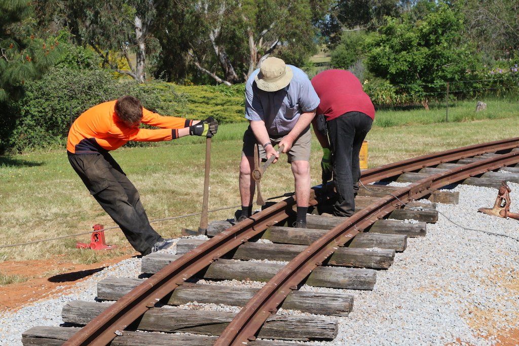 Image 2016.4584: Even I got involved in the trackwork construction. While Rhys levers a sleeper upwards, I'm packing ballast under it. In the background, Rob is drilling sleepers for dog-spiking.