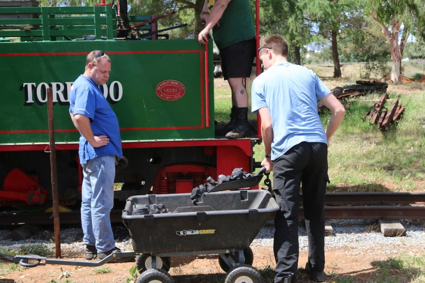 Image 2017.5039: As Ben and Matt look on, Rhys is about to lift the loaded fireman's shovel up to cab height, to be dropped into the bunker.