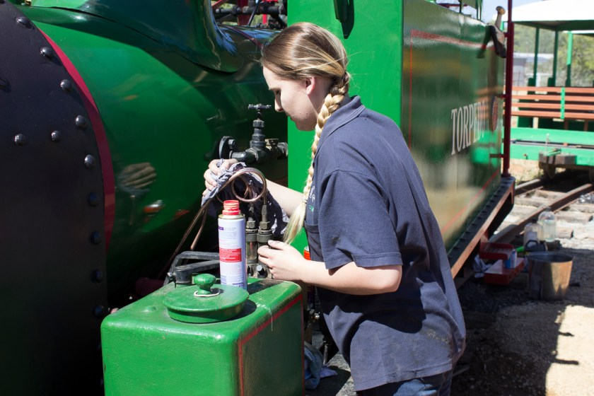 Image T0252: It takes time to raise steam so loco beautification continues. Jasmine makes sure that the mechanical lubricator piping is shining!