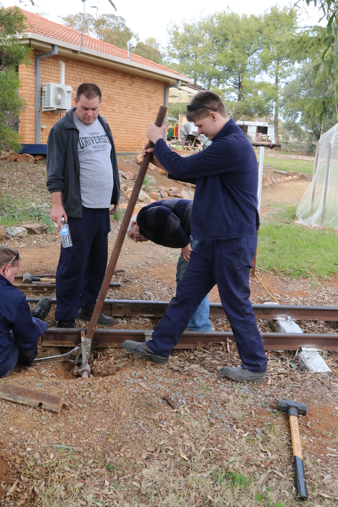 Image 2018.1455: Manually drilling through a rail is hard work. Rhys uses an old boiler tube in order to provide additional leverage... not always successful as we did succeed in snapping one drill! Ben can just be seen at left, sitting on a large spanner in order to prevent contra-movements of the drill. Dave and Gordon look on. The white-painted sleeper at right marks a Block Post for safe-working purposes.