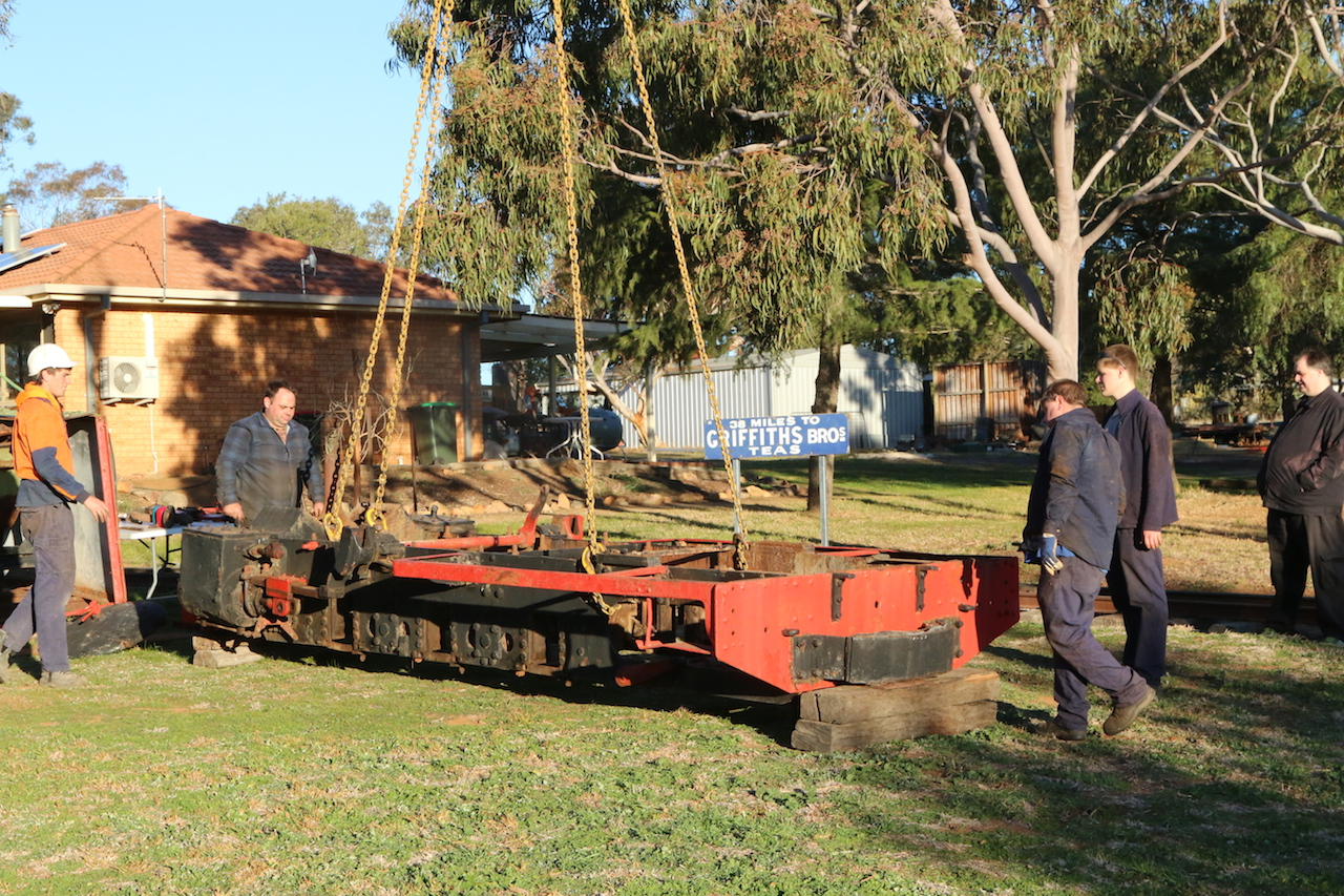 Image 2018.1816: …and lowered on to waiting sleepers. Matt, Ben and Rhys look on. Even our Events Co-Ordinator, who professes to have no interest to railways, dropped around to watch the proceedings.