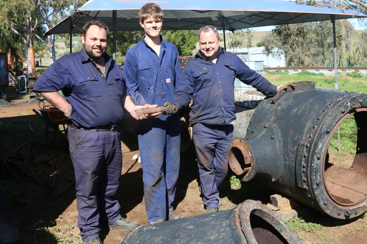 Image 2018-2145: The last segment of 75 tubes removed from the Boiler. Matt, Rhys and Ben all look rather pleased that this part of the project has been completed. Wait until they have to install 75 new tubes! Friday, 7/9/2018.