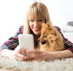 Picture of a small dog and a young woman in the living room