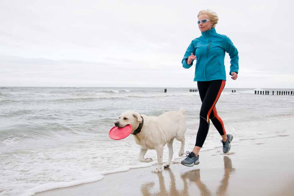 Picture of a woman running on the beach with a dog