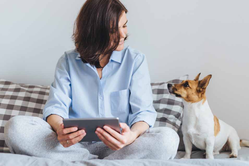Picture of dog looking at a woman that's sitting on the bed