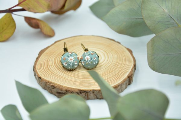 This image is showing a pair of earrings color blue vintage collection on a wood/