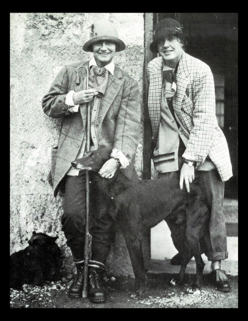 Coco Chanel and Vera Bates stand outside in menswear with two dogs.