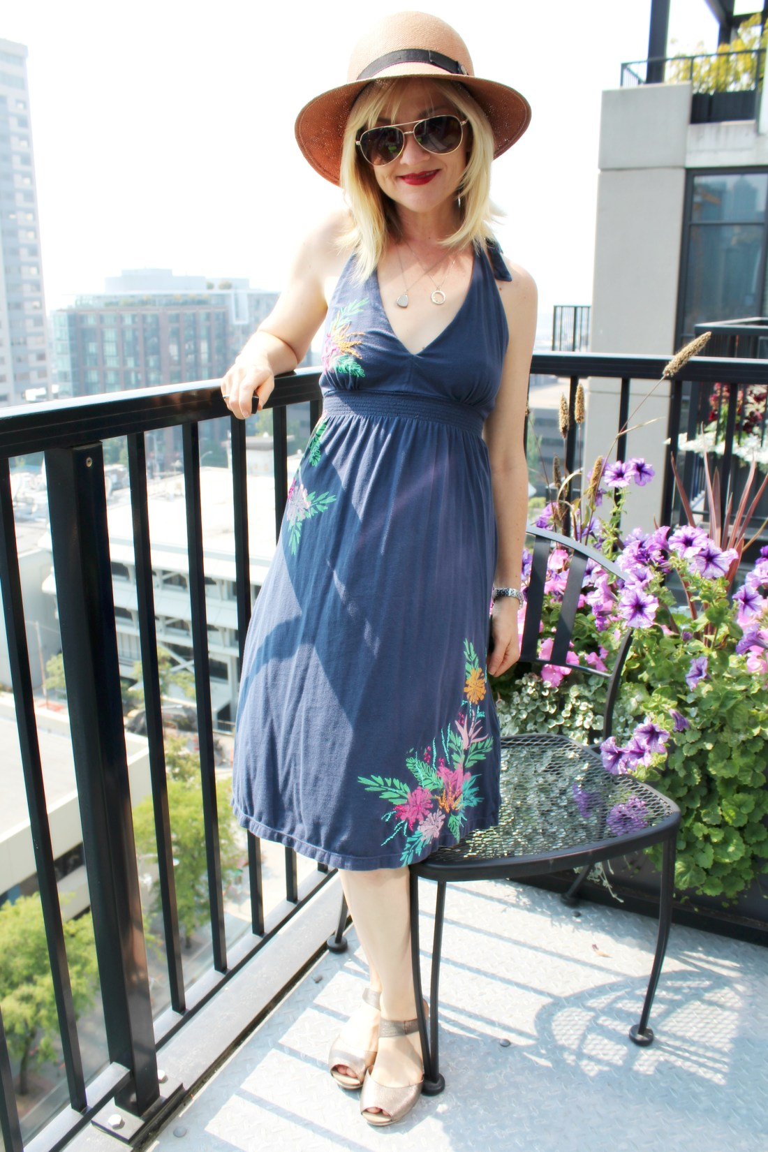 Standing on a balcony wearing a halter dress, a sun hat, sunglasses, and sandals, surrounded by flowers.